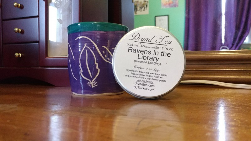 Photo of a handmade mug, with a tin of tea labeled Ravens in the Library.