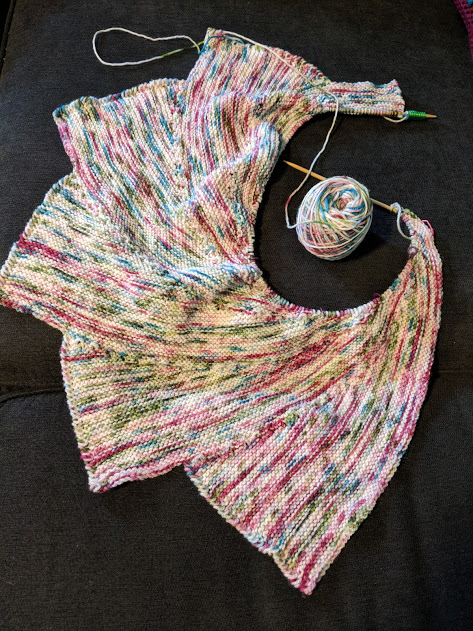 Shawl that somewhat resembles a dragon wing, in shades of cream, pink, blue, and green.
