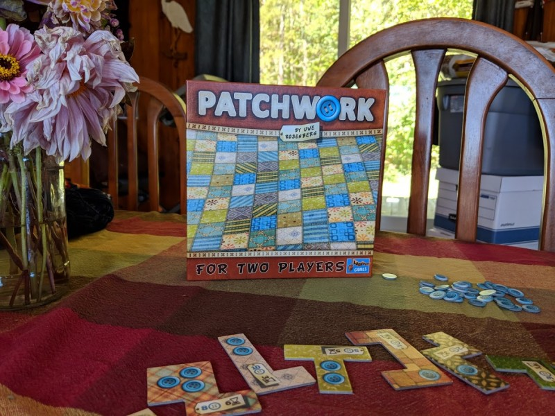 The box for the board game Patchwork, with game pieces surrounding the box.