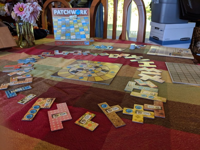 The game Patchwork set up and ready for play, with a square board that keeps track of player turns and differently shaped pieces of various colors representing quilt patches surrounding the board.