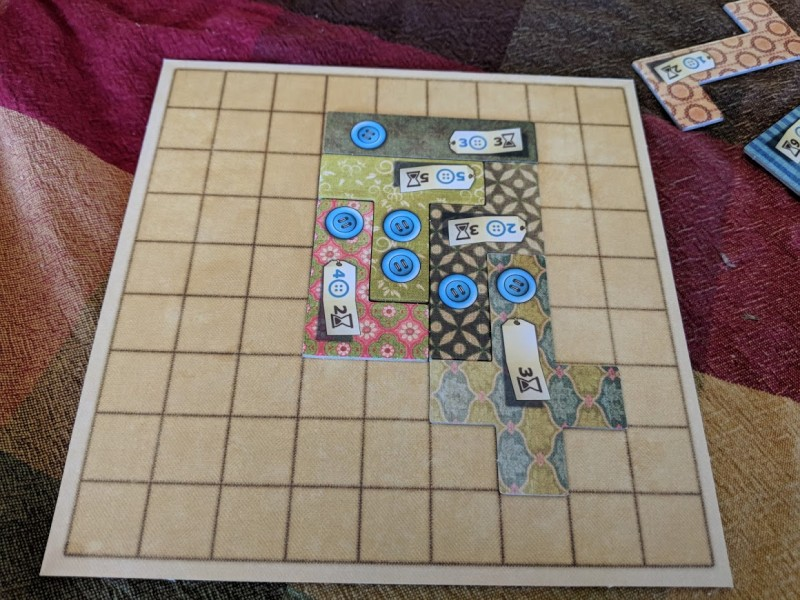 Patchwork game board with a couple of pieces on it, arranged to make a small, irregularly-shaped quilt.