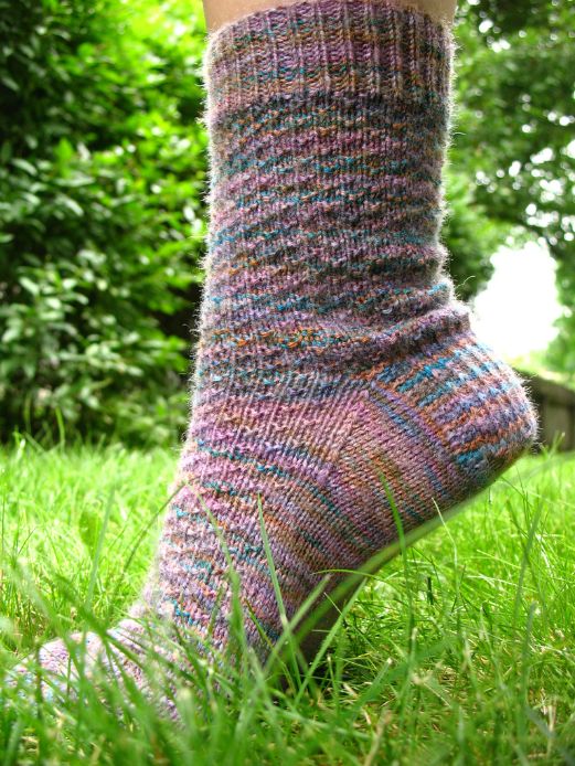 A foot on tiptoe in the grass, showing off a sock made from the Hermione's Everyday Sock pattern