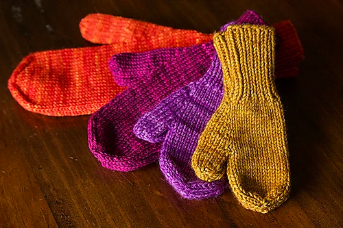 A set of four knit mittens in different sizes and colors.