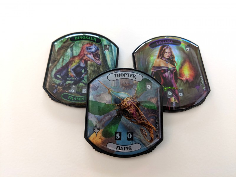 Three Magic: The Gathering token counters - one with a dinosaur on it, another with a thopter, and the third with Liliana.