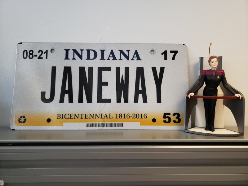 A June 2019 nerdy tidbit: Photo of a Captain Janeway Christmas ornament next to an Indiana vanity license plate that says JANEWAY.