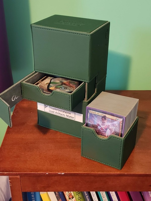 A green, heavy-duty Magic deck box. It holds two decks of cards and also has a tray to hold extra accessories.