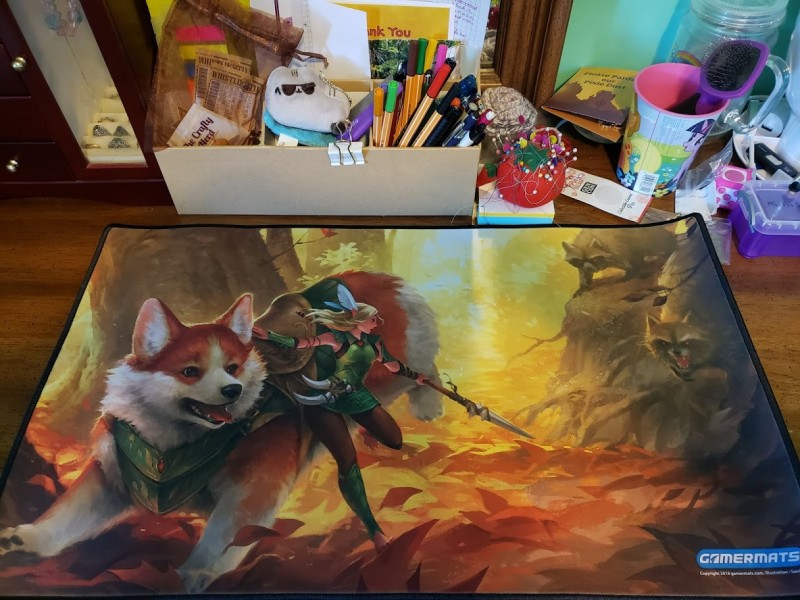 A Magic playmat with a corgi and a faerie about to fight some angry raccoons on it.