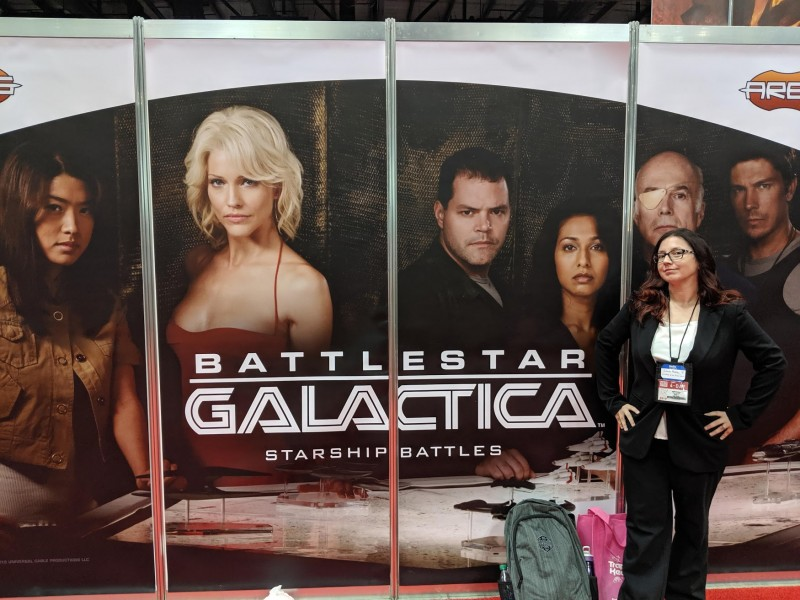 Me dressed as President Roslyn from Battlestar Galactica, in front of a wall with Battlestar Galactica characters on it.