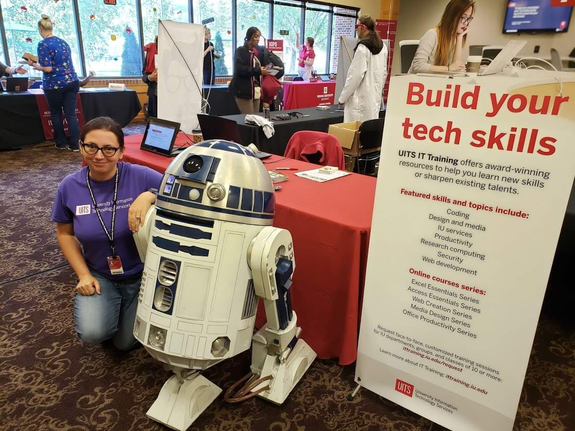 Me kneeling next to a remote-controlled R2-D2 in front of IT Training's booth at Game On.