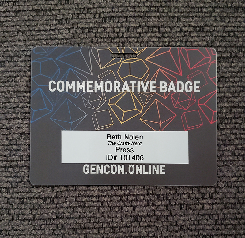 Photo of my Gen Con 2020 commemorative badge. A label with my name, the blog's name, and my Gen Con ID number printed on it has been applied to the back.