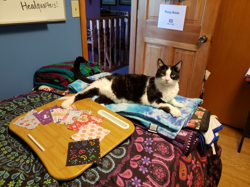 A tuxedo cat laying on a bed in front of a lap desk with fabric squares on top of it.