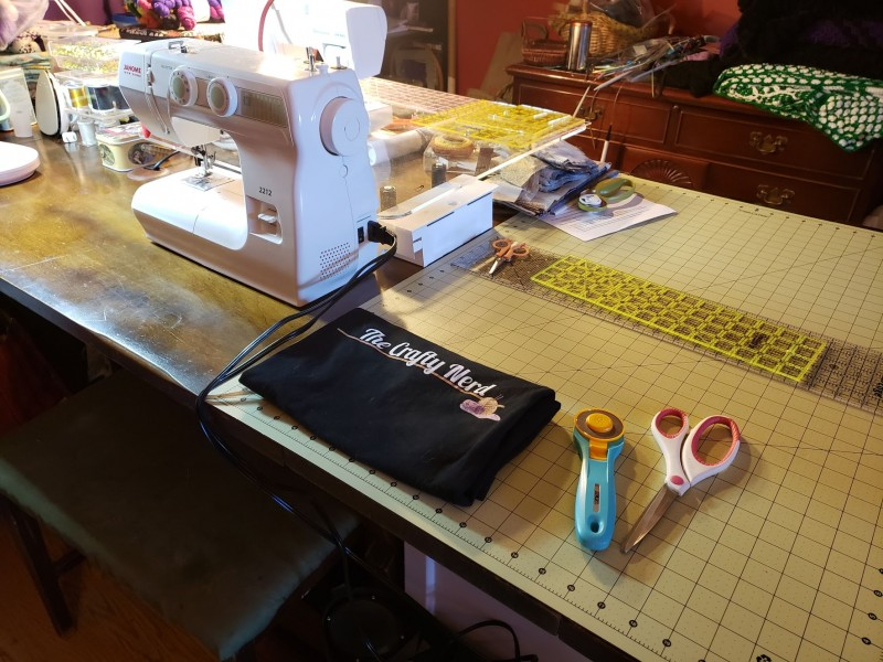 A table with a sewing machine, a Crafty Nerd t-shirt, and some fabric cutting tools laid out on top of it.
