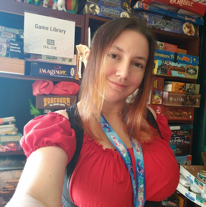 """Me dressed as Elinyr, in front of a bookshelf full of games with a sign saying """"Games Library"""" taped to it."""