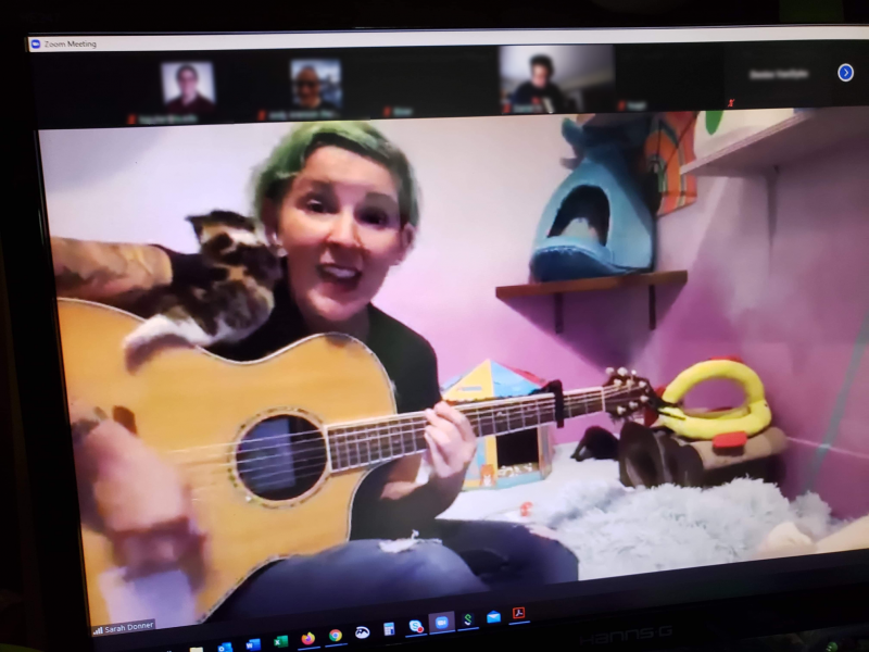 Sarah Donner playing the guitar with a kitten trying to climb on her.